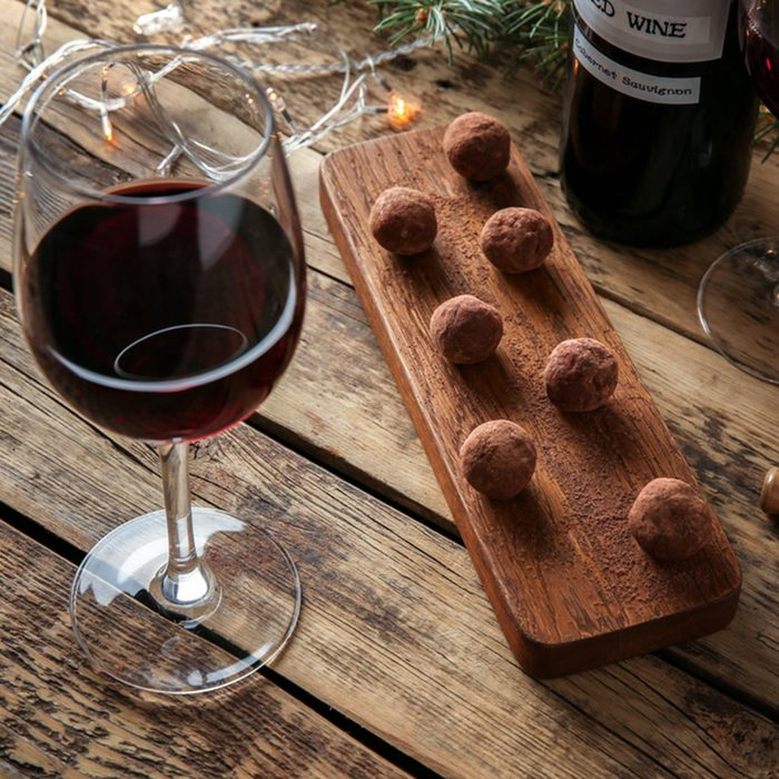 Red wine, chocolate dessert and Christmas decorations on wooden table; Shutterstock ID 600259550