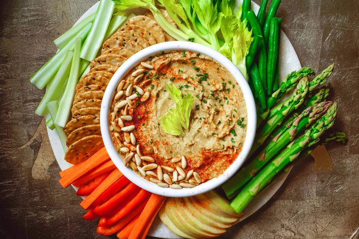 Hummus artichoke platter with assorted snacks, vegetables on stone background. Plate Middle Eastern/Mediterranean dip. Party/finger food. Top view, toning.