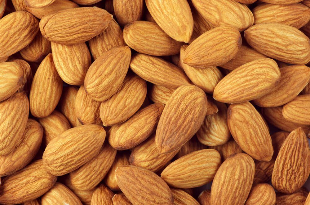 Pile of almonds close-up as background.