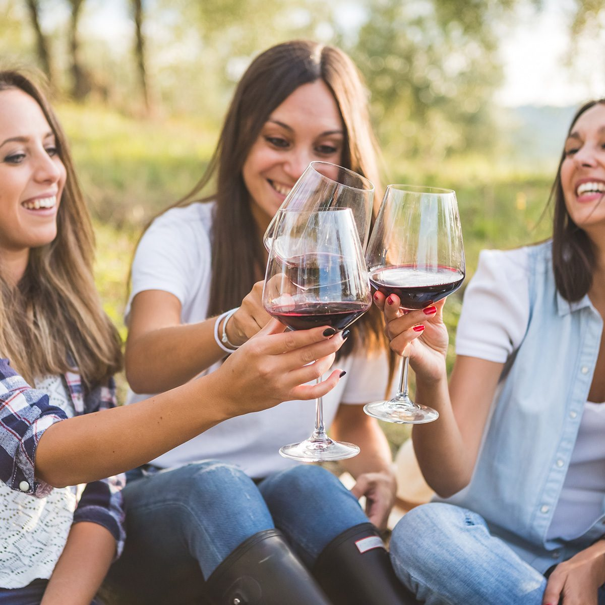 Three happy women toasting with red wine while sitting with basket of grapes in the garden