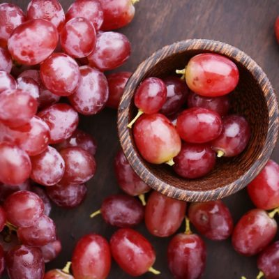 Red grapes on wooden table - vintage filter.