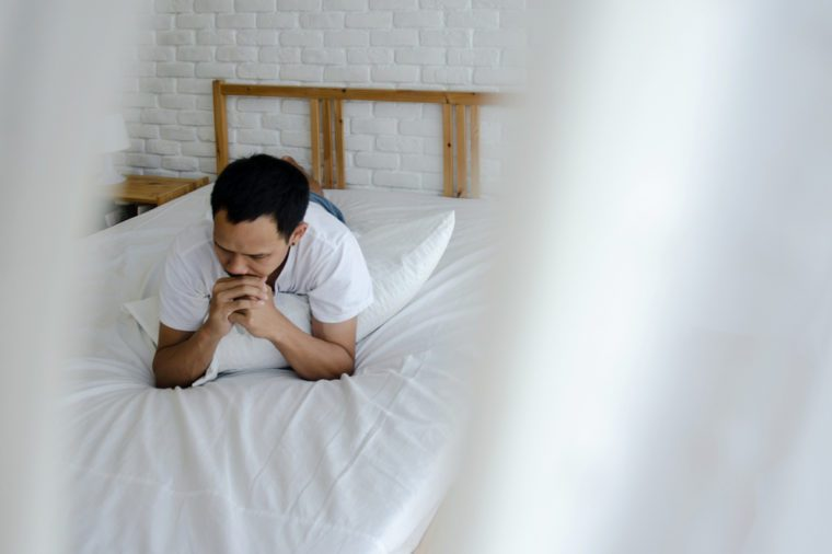 Men are sitting at the edge of the bed in the room and have stress.Young man wearing a white shirt with both hands on his head. Because of pain.Do not focus on objects.