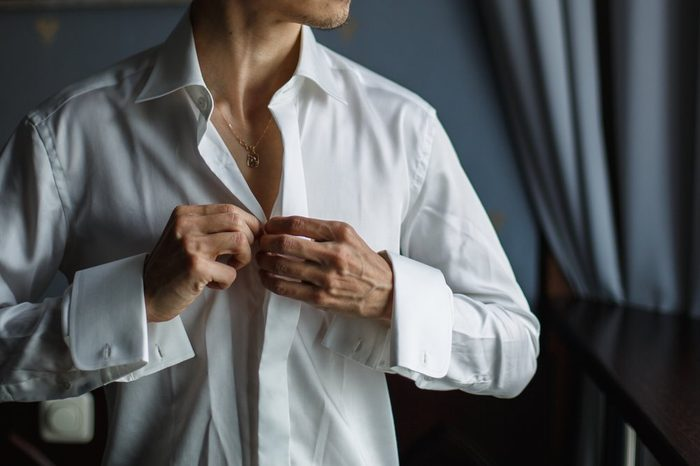 people, business, fashion and clothing concept - close up of man dressing up and fastening buttons on shirt at home