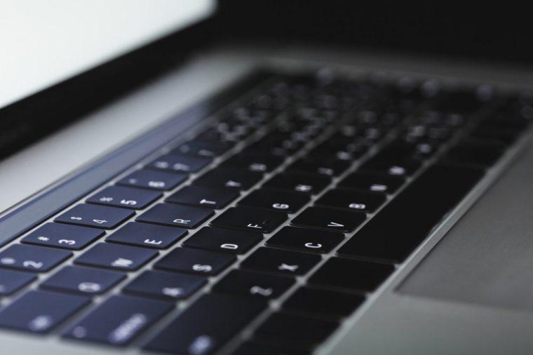 close-up laptop keyboard illuminated on night
