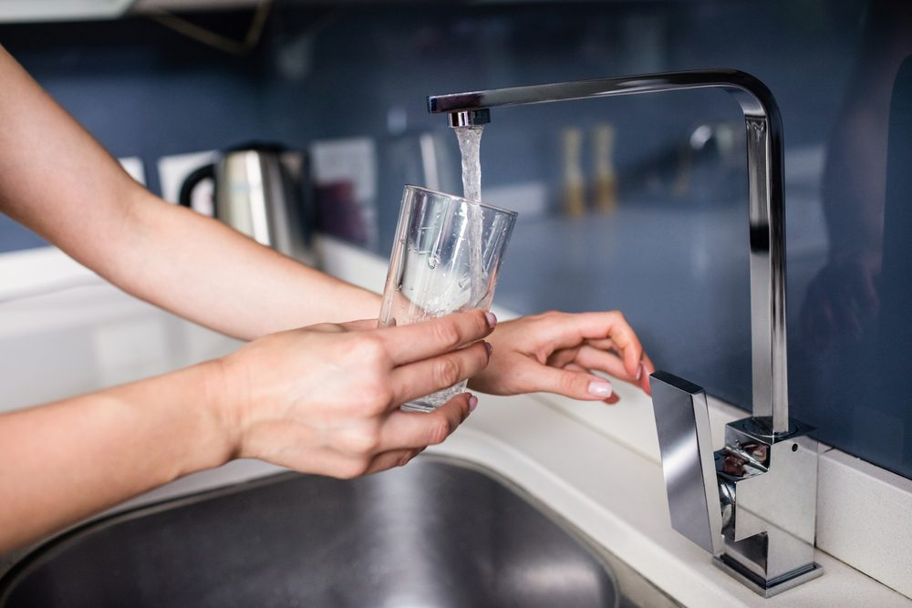Cropped image of woman filling water in glass from faucet at kitchen sink