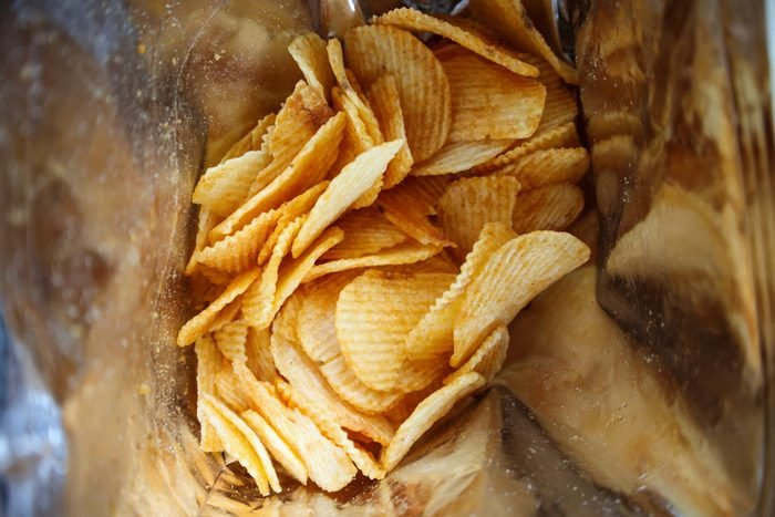 Potato chips in open snack bag close up