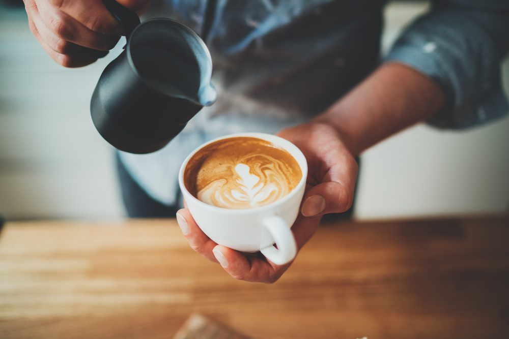 Closeup image of male barista holding and pouring milk for prepare cup of coffee, latte art, vintage color tone, coffee preparation and service concept, lifestyle