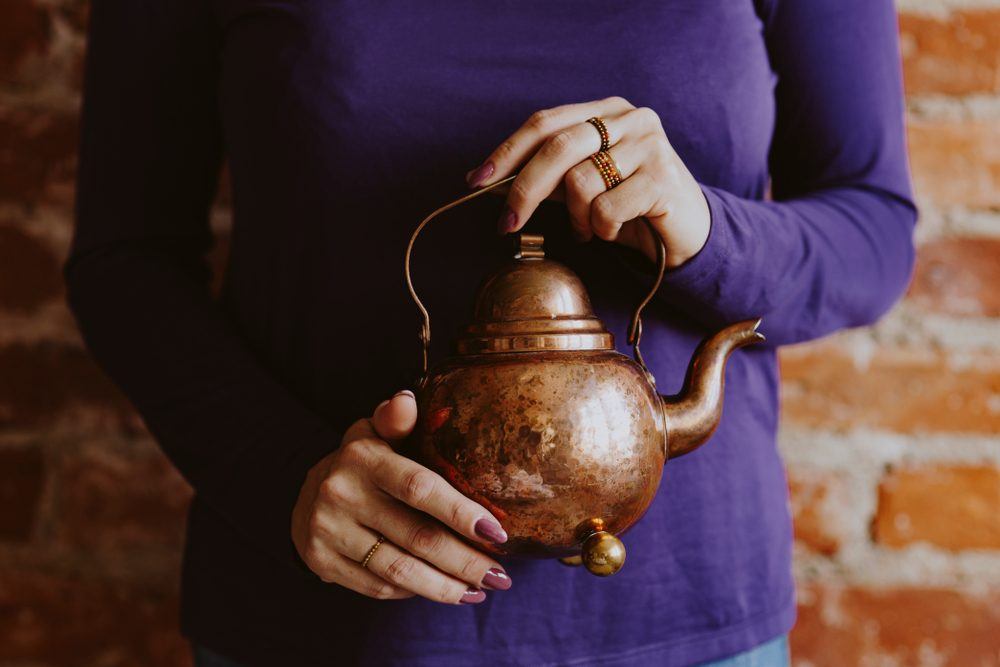 Women holding the small brown teapot