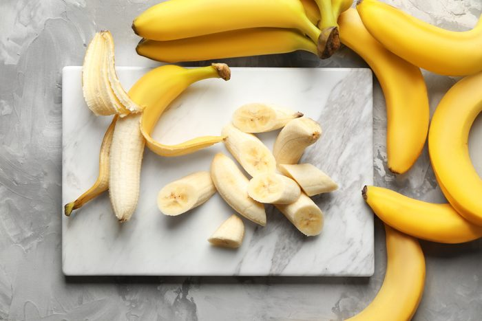 Marble board with sliced bananas on table