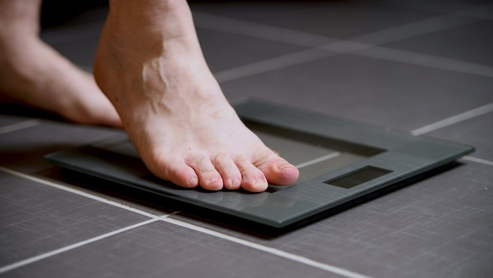 Male feet on glass scales, men's diet, body weight, close up, stepping on digital scale, sport and lifestyle concept