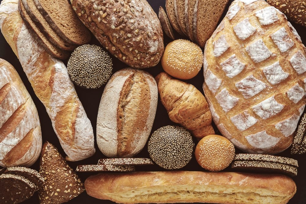 Bread background, top view of white, black and rye loaves on black