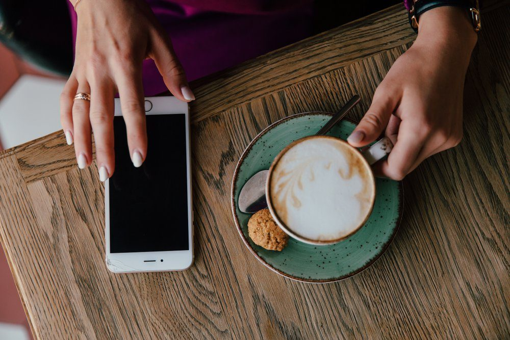 Female hands hold a cell phone and a cappuccino cup on a saucer with a cookie. Against the background of the table. white manicure and telephone. top view Black screen.