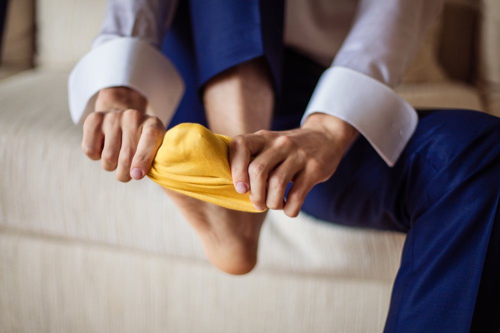 The man wears yellow socks.