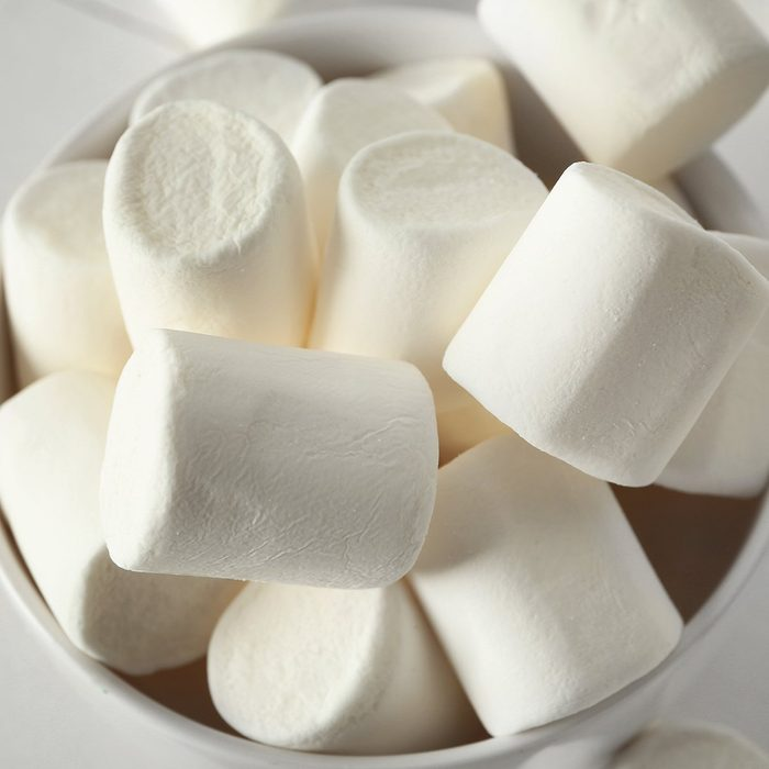 Bowl with tasty marshmallows on white table
