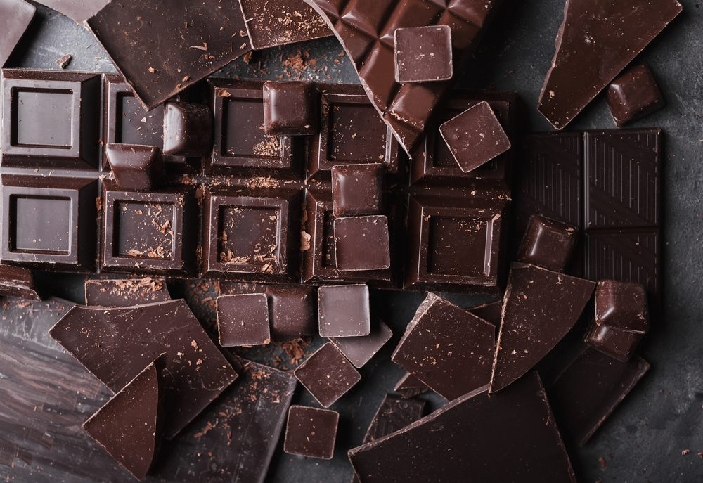 Chocolate bar pieces and candies on gray background close up