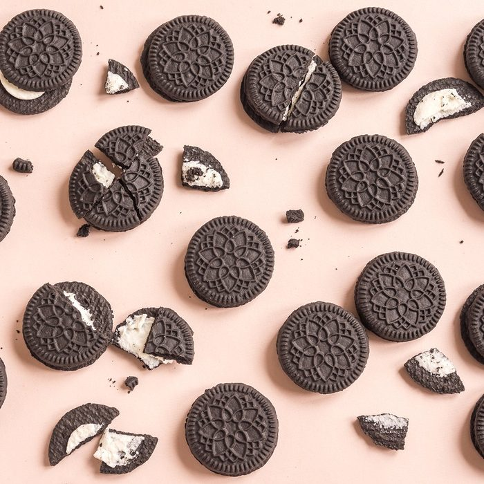 Chocolate and cream sandwich cookies on pink pastel background, top view.