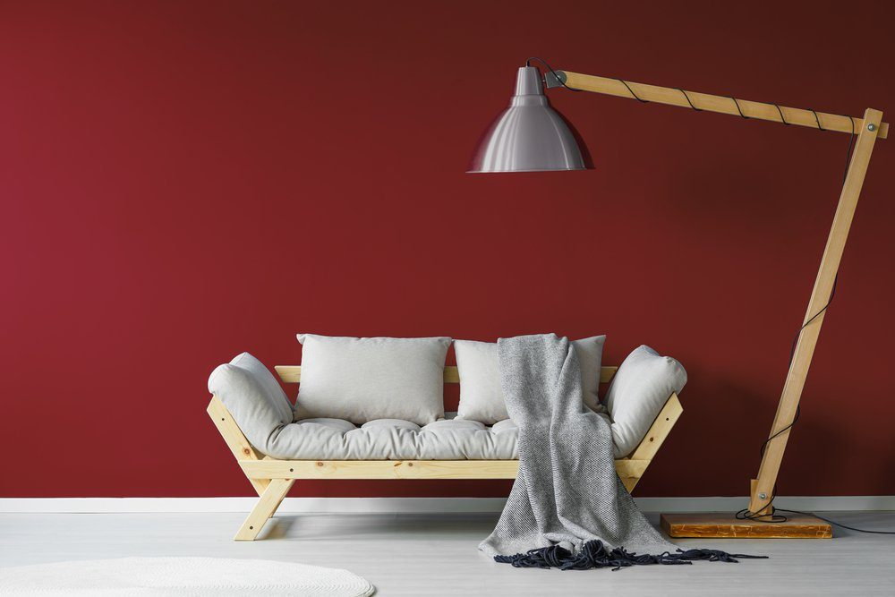 Comfortable couch with a large lamp standing over it in a minimalistic living room interior