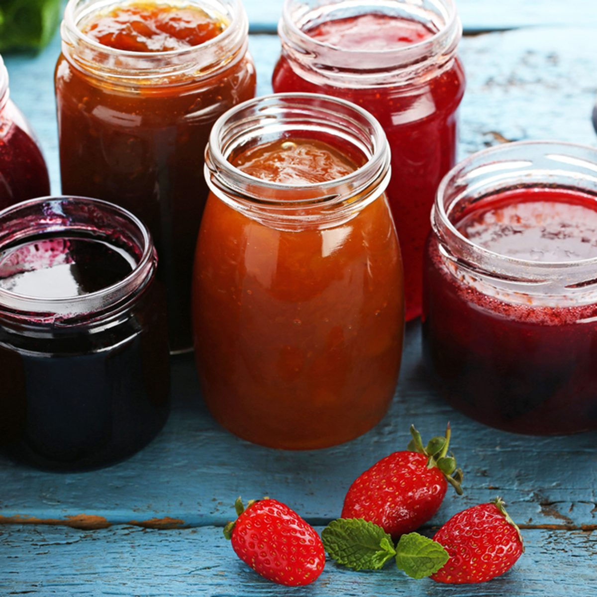 Glass jars with different kinds of jam and berries on wooden table