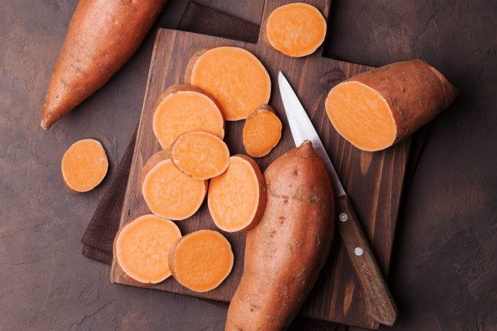 Sweet potato on wooden kitchen board from above.