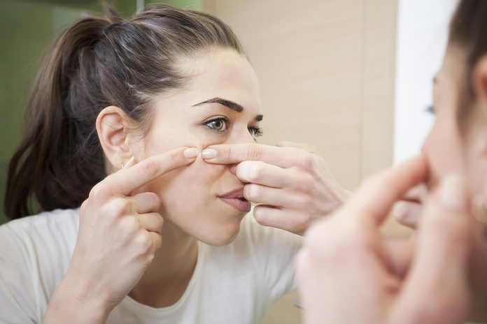 woman looking in the mirror and squeezing a pimple