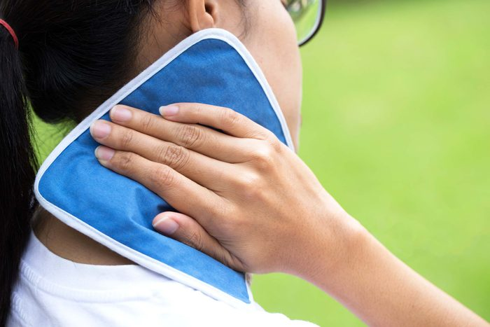 woman holding compress to neck