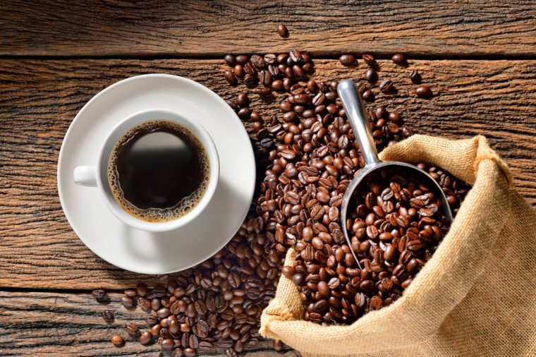 Boost Male Fertility | A cup of coffee on saucer and bag full of coffee beans with scoop
