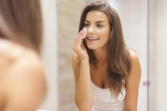 A woman applying a cleansing pad to her skin while standing in front of the mirror. | These skin care ingredients can cause breakouts.