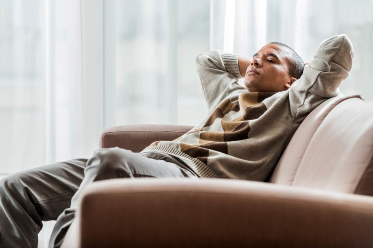 Boost Male Fertility | Man relaxing on couch with eyes closed, hands behind head