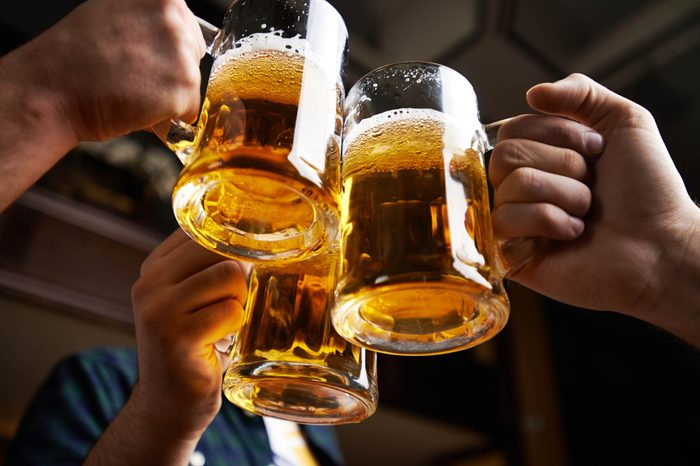 Boost Male Fertility | Hands clinking together three mugs of beer in a toast