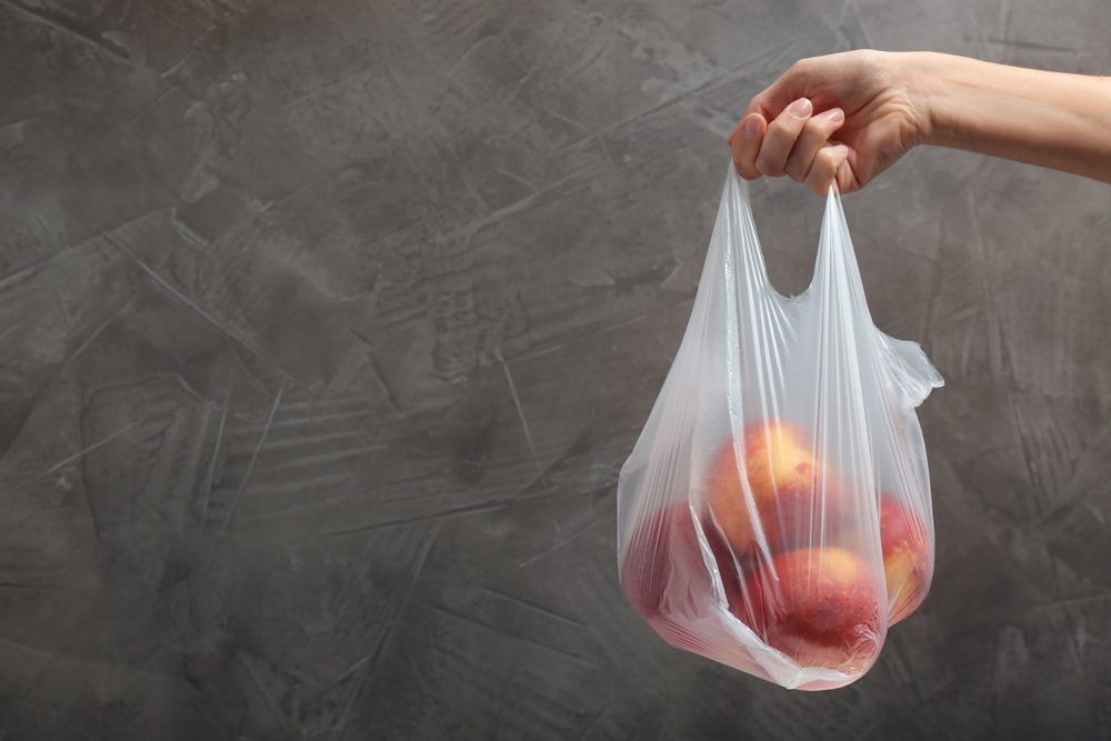 Woman holding plastic bag with apples on gray background. Closeup, space for text
