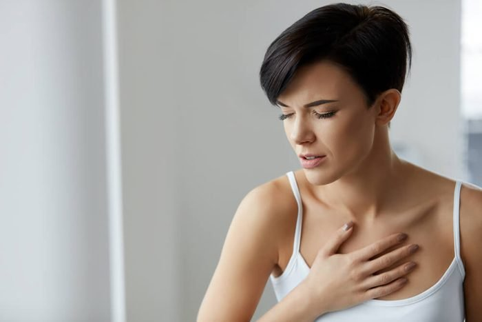 Woman In Pain. Beautiful Young Female Feeling Sharp Strong Pain In Chest. Girl Suffering From Painful Lung Feeling Or Having Heart Attack, Holding Hand On Chest. Health Care Concept. High Resolution