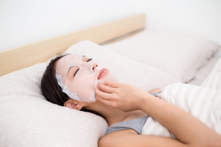 Woman use of the paper mask ans lay on the bed