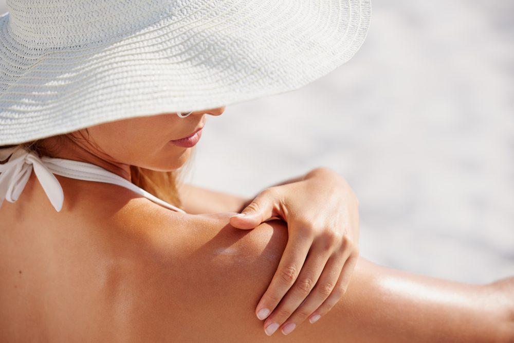 skin cancer   woman applying sun screen