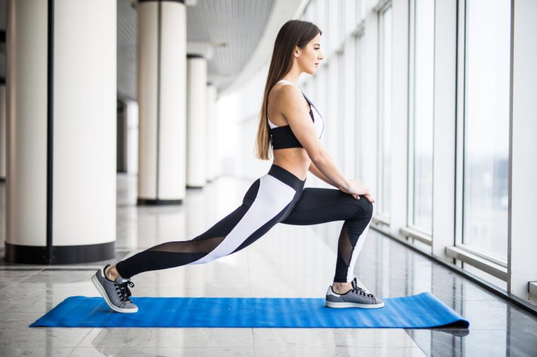 Stretching after great workout. Young beautiful young woman in sportswear doing stretching while standing in front of window at gym