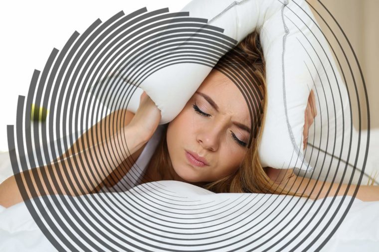 woman holding a pillow over her head, eyes closed