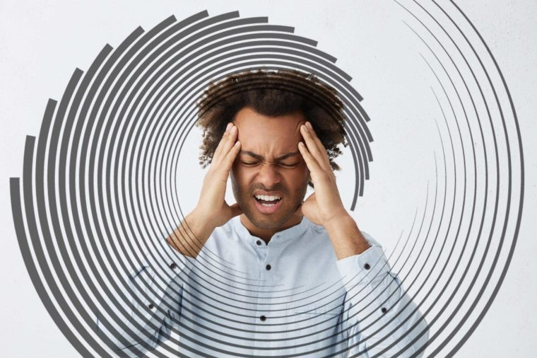 man grimacing and holding his hands to his head