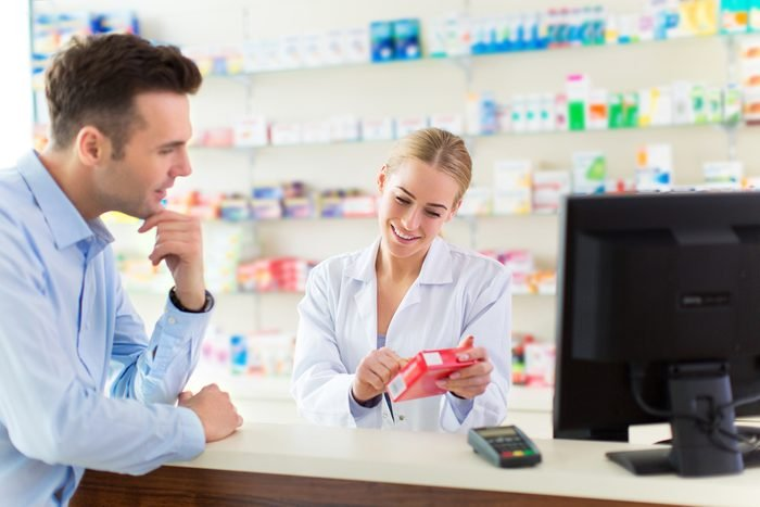 patient talking to pharmacist looking at Rx bottle