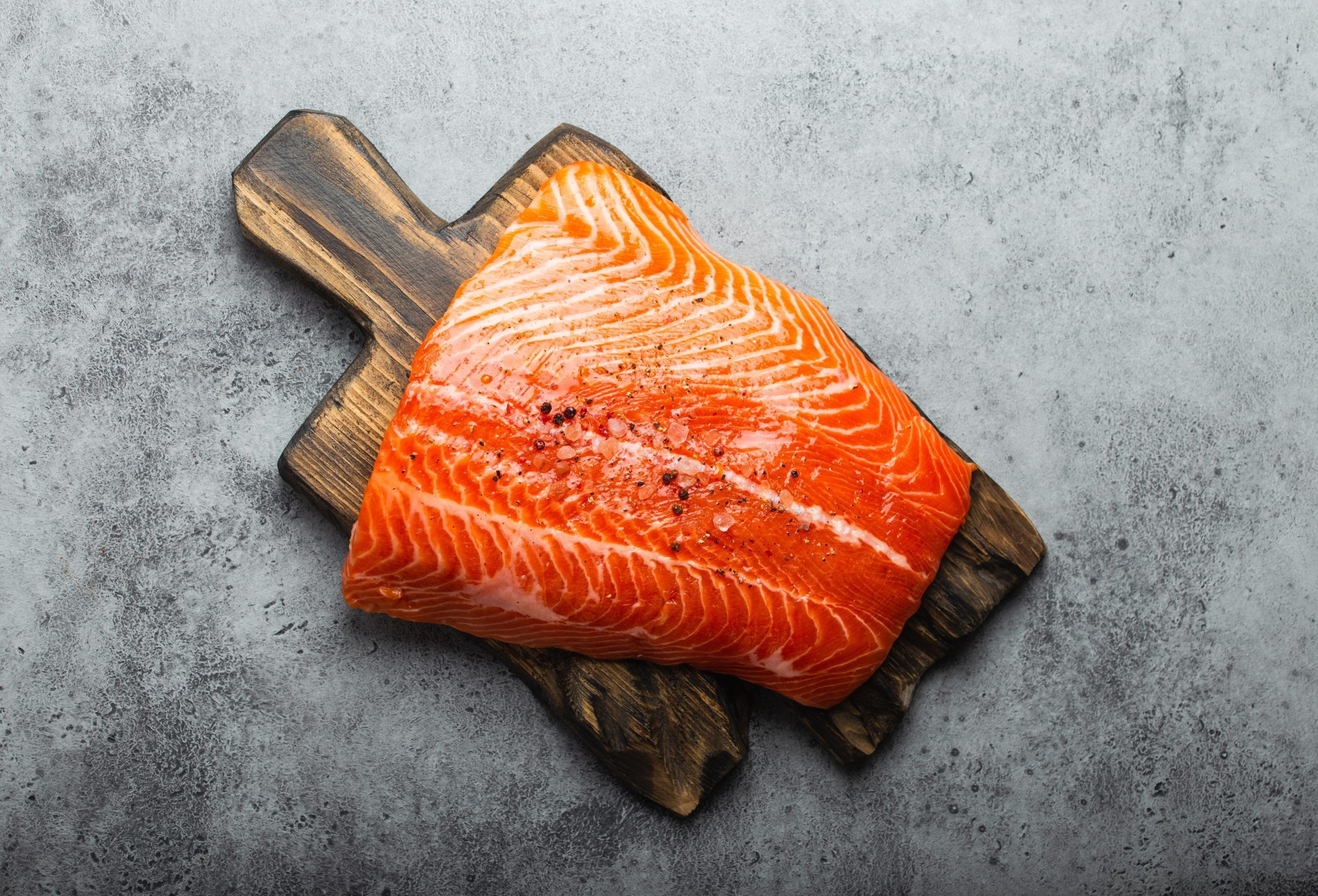 build muscle | fresh raw salmon fillet with seasonings on wooden board, gray stone background. Preparing salmon fillet for cooking, healthy eating concept