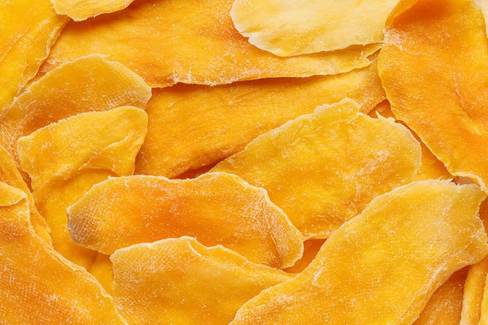 Dehydrated mango as a background. Dried fruits. Natural healthy candy. Top view.