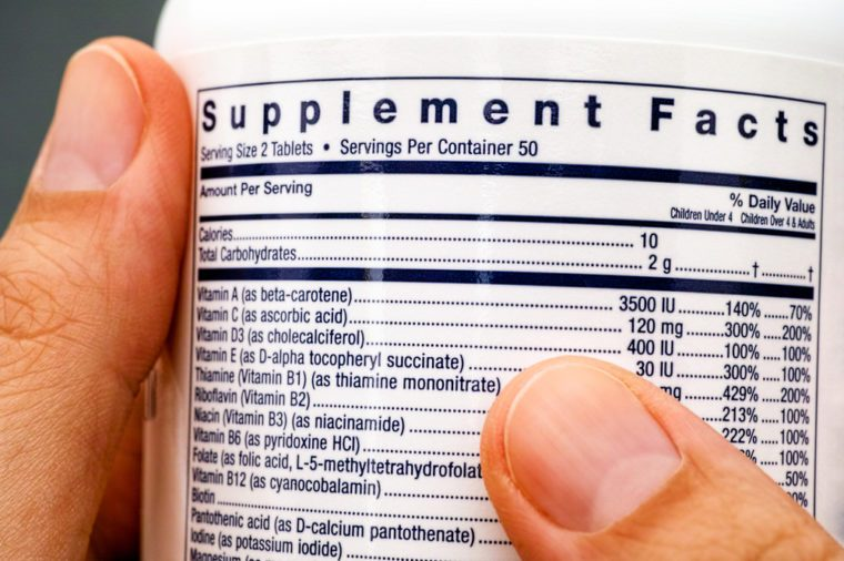 Close-up of white plastic jar with supplement facts of multivitamins in woman hands.