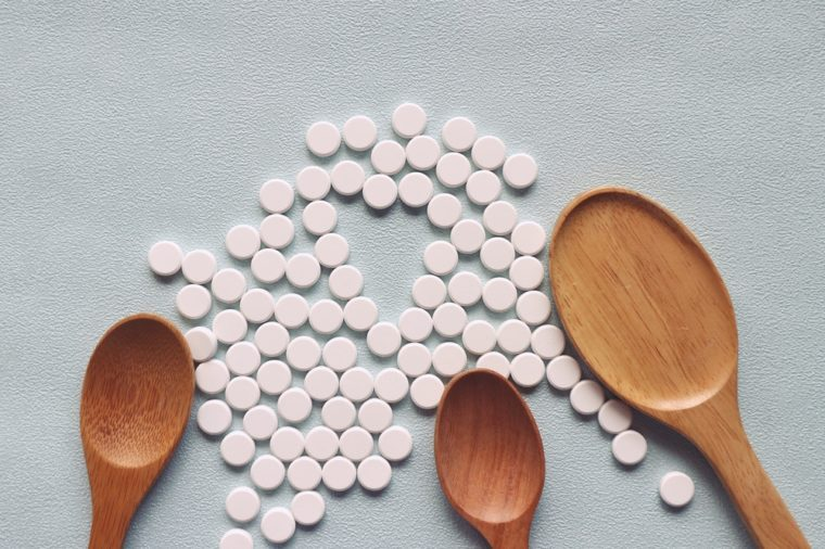 Empty wood spoon and white round pills on light blue background