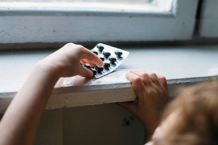 Child takes pack of pills. Dangerous situation. A small child curious about a prescription drug container illustrating the importance of drug safety and parental supervision and communication.