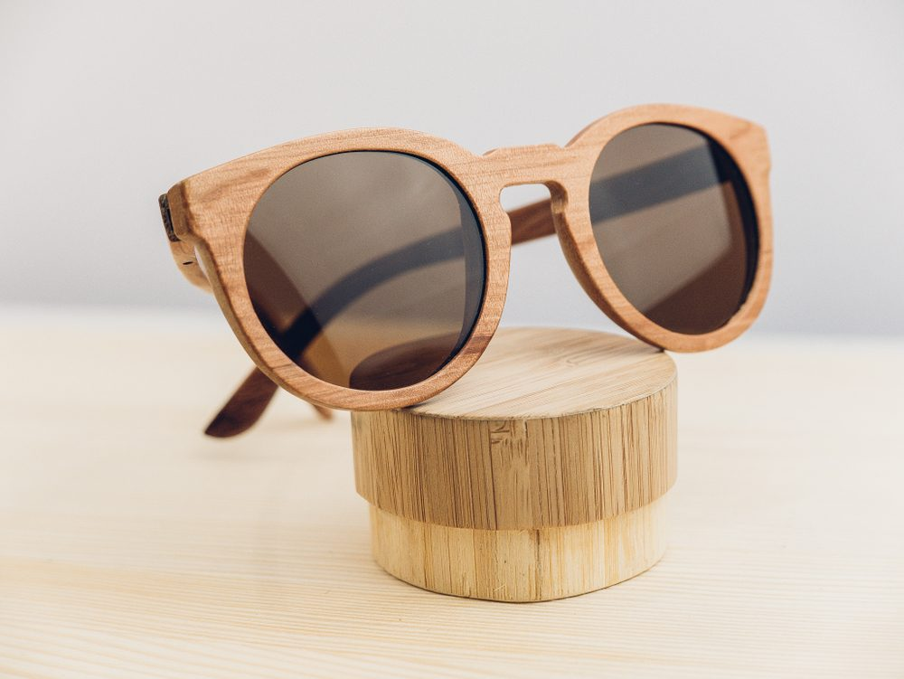 Wooden sunglasses with cover on wooden background, wooden case