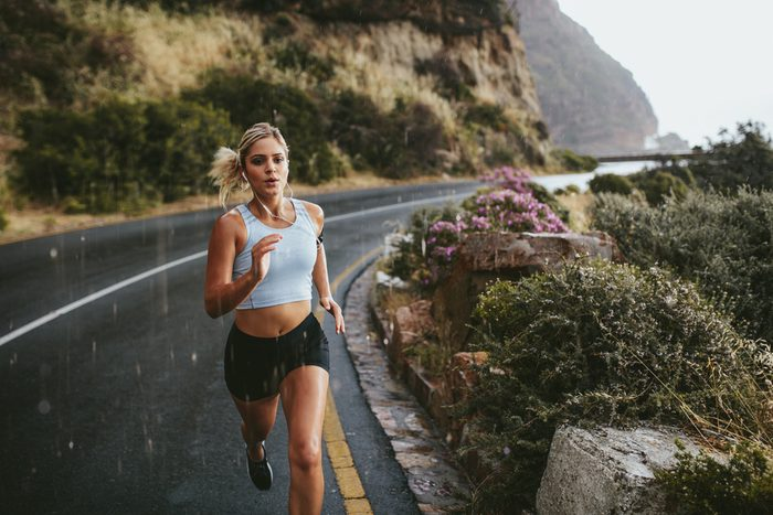 Fitness woman running on highway around the mountains. Female athlete training outdoors during rain.