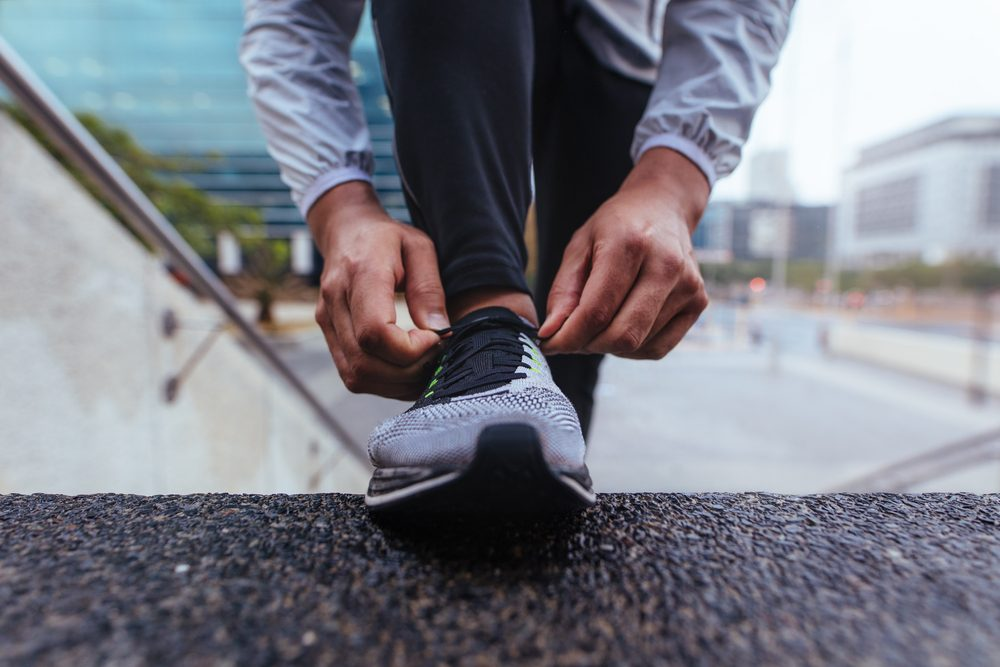 Male runner tying shoe lace on the steps of a building. Closeup of an athlete wearing running shoe.