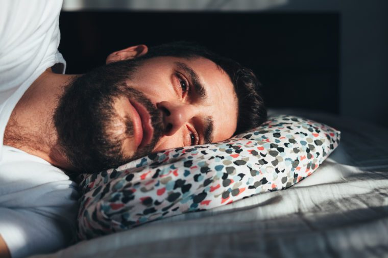 young man crying alone in bed
