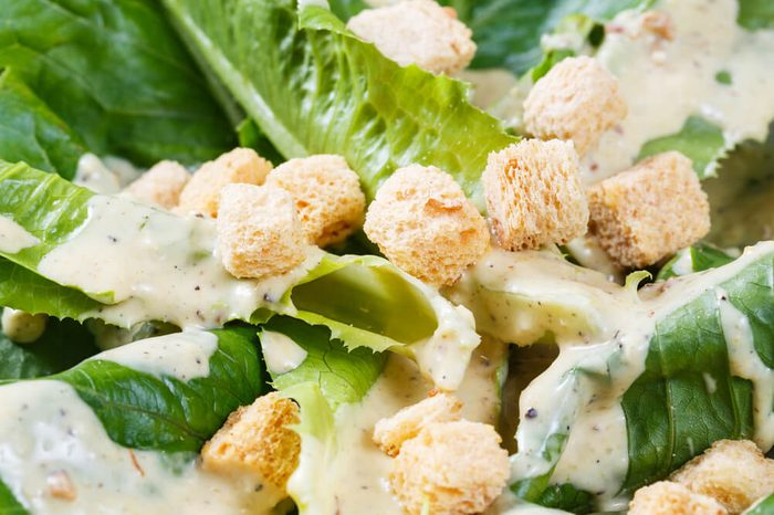 Close up croutons and cos vegetable on caesar salad dish