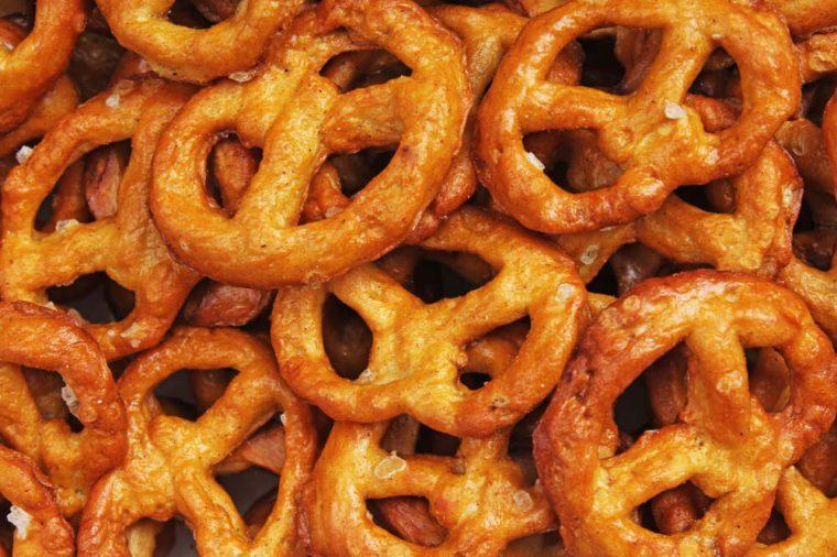 Pretzel shaped bread sticks cracker texture pattern. Salted pretzels. Mini pretzel snack texture.