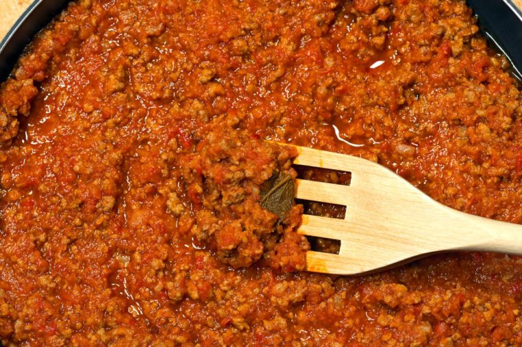 Detail of italian meat sauce (Bolognese or ragu) cooked with vegetables and tomato sauce and a wooden fork