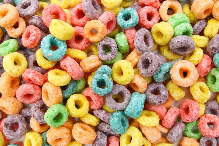 Delicious and nutritious fruit cereal loops flavorful on white background, healthy and funny addition to kids breakfast